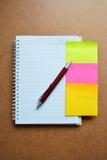 Cuaderno, pluma roja, verde, documento de nota amarillo rosado sobre fondo de madera Imagenes de archivo