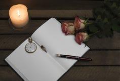 Cuaderno, pluma, rosas de la vela en fondo oscuro foto de archivo libre de regalías