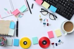 Cuaderno, pluma, teclado, taza de café y accesorios colocados en un wh fotografía de archivo