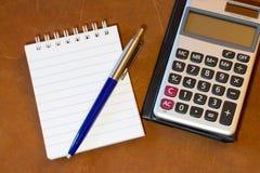 Cuaderno, pluma y calculadora en una tabla Fotos de archivo