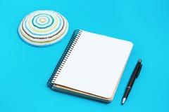 Cuaderno, pluma y kipa en un fondo azul Año Nuevo judío, Rosh Hashanah Imagen de archivo libre de regalías