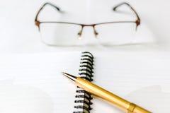 Cuaderno, pluma y lentes imagen de archivo