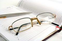 Cuaderno, pluma y lentes Imagen de archivo libre de regalías