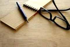 Cuaderno, pluma y lentes Foto de archivo libre de regalías