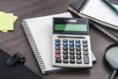 Cuaderno, pluma y lupa con la calculadora en el escritorio Imagenes de archivo