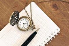 Cuaderno, pluma y reloj en fondo de madera imagen de archivo libre de regalías