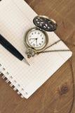 Cuaderno, pluma y reloj en fondo de madera fotografía de archivo libre de regalías