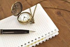 Cuaderno, pluma y reloj en fondo de madera imagenes de archivo