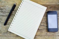 Cuaderno, pluma y smartphone Fotografía de archivo libre de regalías