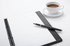 Cuaderno, pluma y taza de café blancos en blanco Fotos de archivo