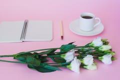 Cuaderno, pluma y taza de café en blanco fotografía de archivo