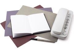 Cuaderno, pluma, y teléfono en el papel texturizado Foto de archivo libre de regalías