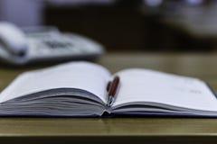 Cuaderno, pluma y teléfono en la tabla Fotografía de archivo libre de regalías