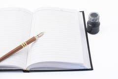 Cuaderno, pluma y tinta Foto de archivo libre de regalías