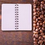 Cuaderno puro para el menú, expediente de la receta en la opinión de sobremesa de madera Granos de café como fondo Imagen de archivo