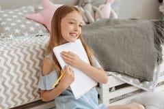 Cuaderno radiante del abarcamiento de la muchacha mientras que dibuja Imagen de archivo