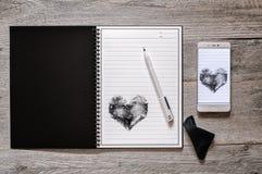 Cuaderno reescribible de papel de piedra y Smartphone imagen de archivo