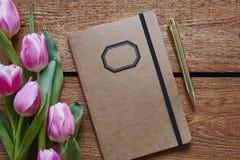 Cuaderno retro y pluma de oro con los tulipanes rosados Fotos de archivo libres de regalías