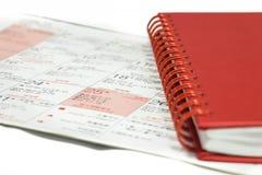 Cuaderno rojo en calendario de la Navidad. imagen de archivo libre de regalías
