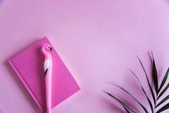 Cuaderno rosado para las notas, la pluma divertida del flamenco y las hojas de palma verdes en fondo en colores pastel rosado End imagenes de archivo