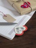 Cuaderno, señal hecha en casa y un regalo hecho a mano del día de tarjeta del día de San Valentín en el papel de Kraft Foto de archivo