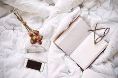 Cuaderno seco de las rosas, del smartphone y del vintage en cama foto de archivo libre de regalías