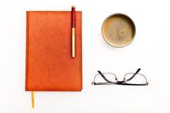 Cuaderno, taza de café, vidrios aislados en el blanco Fotos de archivo libres de regalías