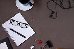 Cuaderno, taza de caf?, vidrios, materiales de oficina fotografía de archivo libre de regalías