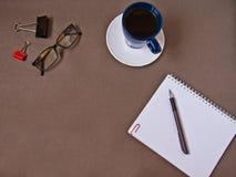 Cuaderno, taza de caf?, vidrios, materiales de oficina imagen de archivo libre de regalías