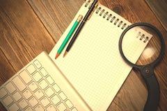 Cuaderno, teclado de ordenador, lupa y un lápiz con Fotografía de archivo libre de regalías
