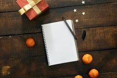 Cuaderno vacío con la caja de regalo roja en fondo de madera Imagen de archivo