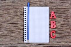 Cuaderno vacío con palabra del lápiz y del ABC en la tabla Imagen de archivo
