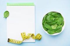 Cuaderno vacío, hojas verdes de la espinaca y cinta métrica en la opinión de sobremesa azul Dieta y concepto sano de la comida imagen de archivo libre de regalías