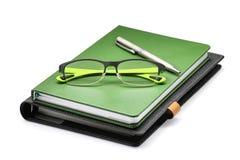Cuaderno verde con los vidrios verdes y la pluma de plata aislados en blanco Fotos de archivo