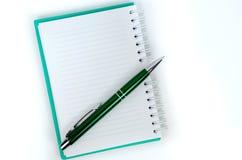 Cuaderno verde con páginas alineadas y una pluma Imagenes de archivo