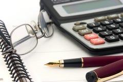 Cuaderno, vidrios, calculadora y pluma Fotos de archivo libres de regalías