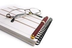 Cuaderno, vidrios y pluma Foto de archivo