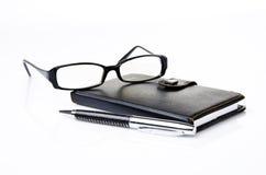 Cuaderno, vidrios y pluma negra imagen de archivo