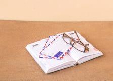 Cuaderno, vidrios y sobre en un fondo de madera Fotos de archivo