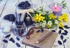Cuaderno viejo, baya madura de la madreselva, vela y wildflowers Imágenes de archivo libres de regalías