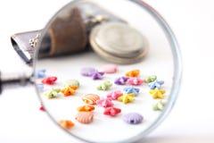 Cuaderno viejo del reloj de la lupa con las gotas multicoloras Fotografía de archivo libre de regalías