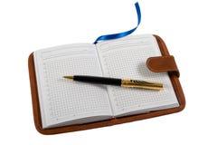 Cuaderno y bolígrafo. Foto de archivo