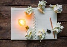 Cuaderno y bombilla Fotografía de archivo libre de regalías