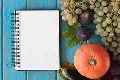 Cuaderno y composición de verduras en el escritorio de madera azul imagen de archivo