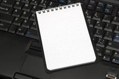 Cuaderno y computadora portátil de la hoja en blanco Imágenes de archivo libres de regalías