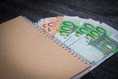 Cuaderno y dinero en la tabla Billetes de banco de la libreta y del euro en fondo de madera oscuro foto de archivo libre de regalías