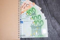 Cuaderno y dinero en la tabla Billetes de banco de la libreta y del euro en fondo de madera oscuro imágenes de archivo libres de regalías