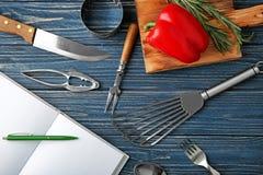 Cuaderno y diversos utensilios de la cocina Fotos de archivo