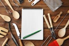 Cuaderno y diversos utensilios de la cocina Imágenes de archivo libres de regalías