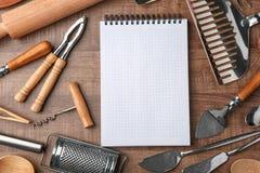 Cuaderno y diversos utensilios de la cocina en fondo Imagen de archivo libre de regalías